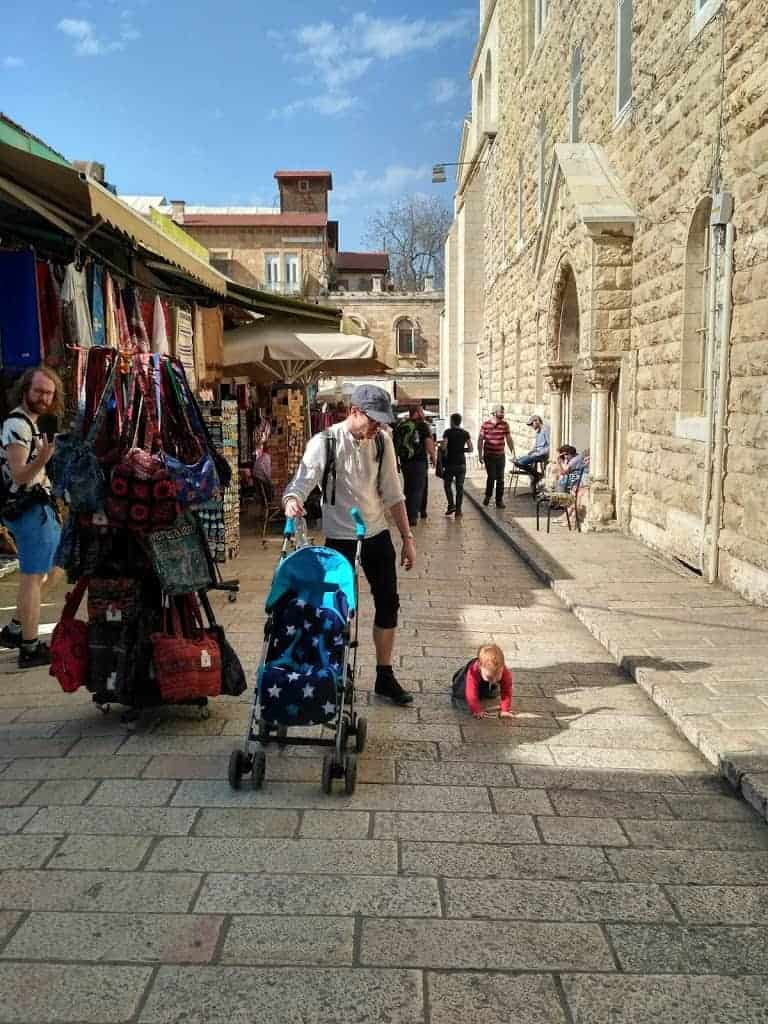 baby crawling on busy street